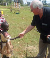 Roger shakes hands with little Bryce Homes girl in March 2014 in Kenya