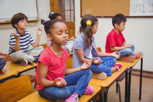Stock photo of children in a classroom meditating: bigstockphoto.com